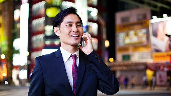 Blurry background with Asian male in suit on cellphone