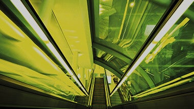 Top to bottom shot of indoor escalator with green color lighting